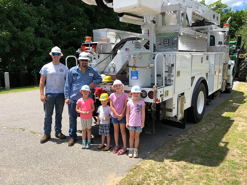 Linemen Jeremy and Jordan with kids outside hte library